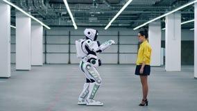 O cyborg alto está vindo a uma senhora e está tocando em sua mão video estoque