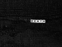 O ` da morte do ` da palavra feito dos cubos em um fundo de madeira preto Fundo preto Fotografia de Stock