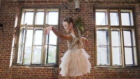 O dançarino bonito gracioso da menina no tutu-vestido executa elementos do balé clássico no estúdio do projeto do sótão clássico video estoque