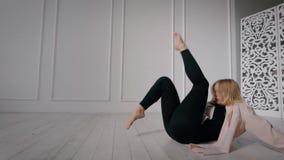 O dançarino contemporâneo fêmea está treinando no salão de dança apenas, sentando-se no assoalho, os pés moventes acima video estoque