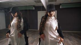 O dançarino da menina executa uma dança moderna ao estar perto do espelho no estúdio da dança Ensaio da dança antes do vídeos de arquivo