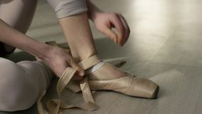 O dançarino de bailado amarra acima seus pointes Dançarino de bailado que amarra sapatas de bailado antes de treinar vídeos de arquivo