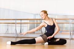 O dançarino de bailado de dobra estica-se no assoalho de madeira imagem de stock royalty free