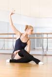 O dançarino de bailado faz os exercícios que sentam-se no assoalho foto de stock royalty free