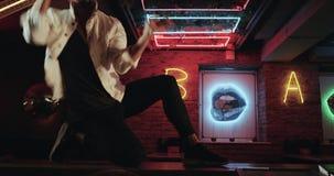 O dançarino dos homens novos mostra o movimento bonito da dança na tabela da barra no café escuro video estoque