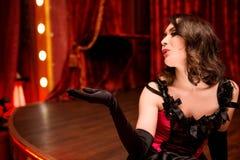 O dançarino elegante no estilo do vermelho do moulin envia um beijo do ar da fase foto de stock royalty free