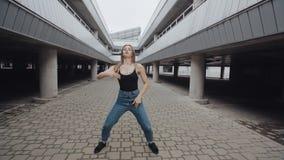 O dançarino fêmea está executando a dança moderna da moda ou do hip-hop, levantar, torcendo o estilo livre em industrial vídeos de arquivo