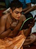 O dançarino indiano tradicional aplica a pintura a sua cara antes do sho Foto de Stock