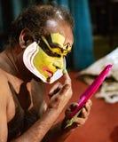 O dançarino indiano tradicional aplica a pintura a sua cara antes do sho Fotografia de Stock