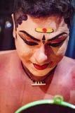 O dançarino indiano tradicional aplica a pintura a sua cara antes do sho Imagens de Stock Royalty Free