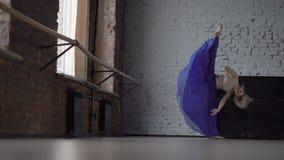 O dançarino louro na saia azul faz a separação em um pé no movimento lento filme