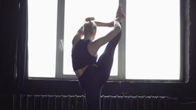 O dançarino louro novo faz a separação em um pé no movimento lento video estoque