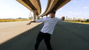 O dançarino masculino novo no chapéu e em dança listrada do t-shirt sob a ponte, vai à câmera vídeos de arquivo