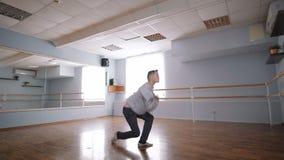 O dançarino novo está ensaiando a dança para um desempenho Grande estúdio espaçoso da dança Janela e grande espelho no filme