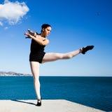 O dançarino novo flexível faz as separações em um bloco de pedra grande Imagens de Stock Royalty Free