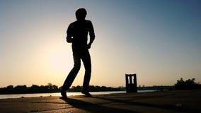 O dançarino novo mostra o disco em um banco de rio no por do sol no slo-mo filme