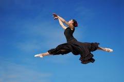 O dançarino que salta de encontro à SK azul Fotografia de Stock