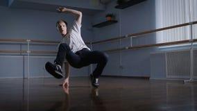 O dançarino talentoso executa movimentos acrobáticos complexos do breakdance Desempenhos da dança no assoalho em um espaçoso vídeos de arquivo