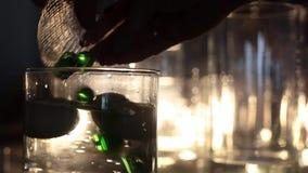 O decorador põe bolas de vidro verdes à água no vaso video estoque