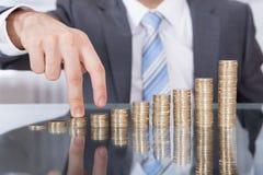 O dedo do homem de negócios vai acima à moeda da pilha Fotografia de Stock Royalty Free