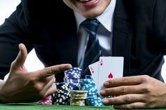 O dedo do uso do jogador do pôquer que aponta a um par de áss e de posse Fotos de Stock Royalty Free