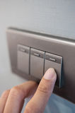 O dedo está girando o interruptor da luz fotografia de stock