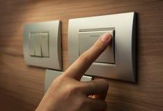 O dedo está girando sobre um interruptor da luz cinzento foto de stock royalty free