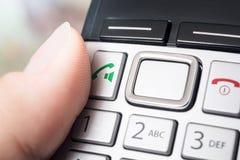 O dedo masculino no botão da chamada do DECT sem fio Telefphone, apronta-se para discar ou ativar a função do Speakerphone fotografia de stock royalty free
