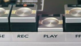 O dedo pressiona botões do controle do playback no jogador de cassete áudio filme