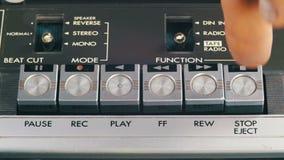 O dedo pressiona botões do jogo, da parada e do controle do registro no jogador de cassete áudio video estoque