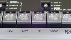O dedo pressiona para a frente e botões do controle da rebobinação no jogador de cassete áudio video estoque