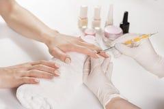 O dedo profissional prega o lustro no estúdio do tratamento de mãos nas mãos da jovem mulher imagens de stock royalty free