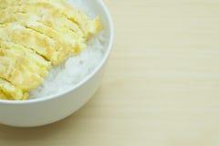 O delicado ferveu o arroz e a omeleta na bacia na tabela de madeira Foto de Stock Royalty Free