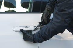 o delinquente no preto está tentando abrir a porta de um carro branco fotografia de stock
