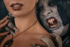 O demônio antigo do vampiro do monstro morde um pescoço da mulher Dia das Bruxas fant fotos de stock royalty free