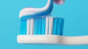 O dentífrico espremeu na escova de dentes, higiene oral, prevenção da chapa, close up video estoque