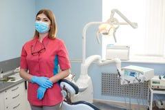 O dentista da menina está no meio de seu equipamento e de olhar a câmera Foto de Stock Royalty Free