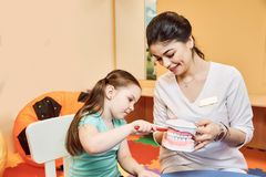 O dentista da mulher ensina a menina escovar seus dentes imagens de stock royalty free