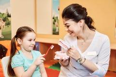 O dentista da mulher ensina a menina escovar seus dentes imagem de stock royalty free