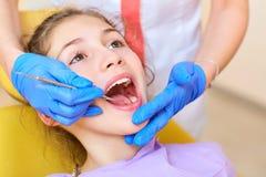 O dentista da mulher trata seus dentes do ` s da criança foto de stock