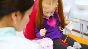 O dentista das crianças e a menina do paciente-um com o cabelo vermelho que joga com o dental do brinquedo instrumento-moldado do video estoque