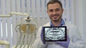 O dentista demonstra o raio X dos dentes humanos em sua tabuleta imagens de stock royalty free