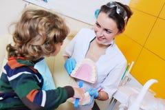 O dentista diz a criança sobre a higiene oral imagem de stock