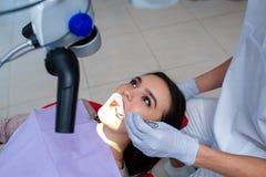 O dentista do doutor trata os dentes de um paciente bonito da moça A menina na recepção no dentista de Doctor do dentista fotos de stock royalty free