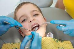 O dentista e a enfermeira estão curando um paciente do rapaz pequeno fotos de stock royalty free
