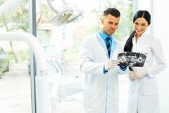 O dentista e o assistente fêmea estão discutindo a imagem dental de X Ray imagens de stock royalty free