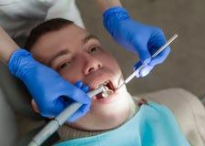 O dentista está fazendo procedimentos do tratamento no escritório dental Imagem de Stock Royalty Free