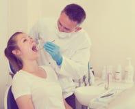 O dentista está tratando o paciente fêmea que se está sentando no ch dental imagem de stock