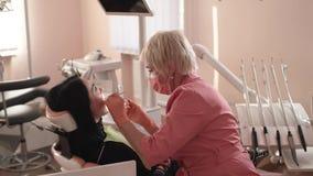 O dentista examina e cura os dentes vídeos de arquivo