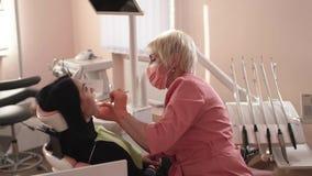 O dentista examina e cura os dentes video estoque